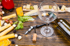 Bottle of Wine and Glass on Table with Cheeses Royalty Free Stock Image