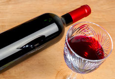 Bottle of wine and a glass on a wooden table Royalty Free Stock Photos
