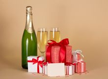 Bottle and wine glasses with champagne, gift boxes Stock Photos