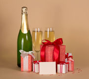 Bottle and wine glasses with gifts Stock Image
