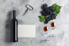 Bottle of wine glasses grape corkscrew empty card mockup. Bottle of wine two glasses grape with leaves, corkscrew, white empty card mockup for your logotype or royalty free stock photos