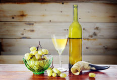 Bottle of wine and grape against wooden surface Stock Images