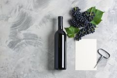 Bottle of wine grape leaves corkscrew empty card mockup. Bottle of wine grape with leaves, corkscrew, white empty card mockup for your logotype or text on grey stock photography