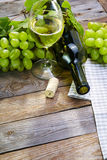 A bottle of  wine with grape on old wooden cutting board Stock Image