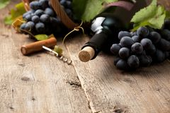 Bottle of wine. And grapes in basket on old wooden background stock image