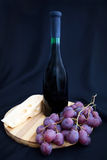 Bottle of wine, grapes and cheese on the board Royalty Free Stock Photography