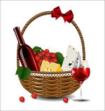 A bottle of wine, grapes and cheese in a wicker basket. Stock Photos