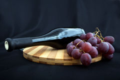 Bottle of wine and grapes lying on a board Royalty Free Stock Image