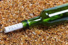 Bottle of wine with help message on wet beach. Bottle of wine with help message driven ashore on wet sand beach at sun summer day Royalty Free Stock Photos