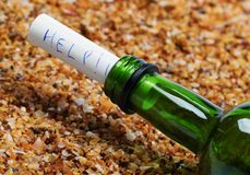 Bottle of wine with help message on sand in beach at sun summer. Day. Close up view Stock Photos