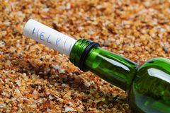 Bottle of wine with help message on sand in beach at sun summer. Day. Close-up view Royalty Free Stock Photos