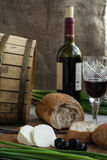 Bottle of wine, olives, cheese and bread are on sacking. Bottle of wine, olives, cheese and white bread are on sacking Royalty Free Stock Image