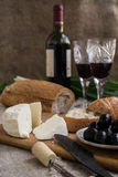 Bottle of wine, olives, cheese and bread are on sacking. Bottle of wine, olives, cheese and white bread are on sacking Stock Photos