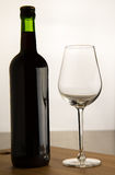 Bottle of wine and one glass. Bottle of wine and glass on wood surface and white background Stock Photo