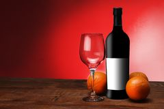 A bottle of wine with oranges. And a glass stock images