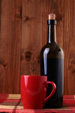 Bottle of wine and red cup. Bottle of red wine and red cup on wooden background Stock Photos