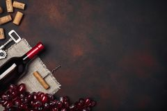 Bottle of wine, red grapes, corkscrew and corks, on rusty background top view royalty free stock photos