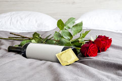 Bottle of wine, roses and condom on bed - sexy set Stock Photos