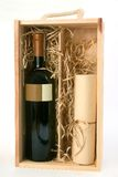 A bottle of wine and a scroll. In wooden box Royalty Free Stock Images