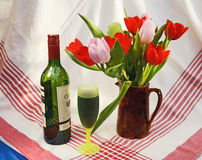 Bottle of wine and Spring tulips. Bottle of wine and green glass with fresh Spring tulips on red striped table cloth Royalty Free Stock Photo