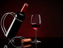 Bottle with wine on a stand and glass Stock Image
