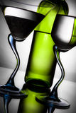 Bottle of wine and two glasses. Bottle of wine and two wine glasses on a graceful leg with reflection Royalty Free Stock Image