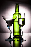 Bottle of wine and two glasses. Bottle of wine and two wine glasses on a graceful leg with reflection Stock Photography