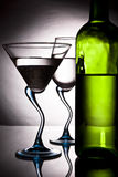 Bottle of wine and two glasses. Bottle of wine and two wine glasses on a graceful leg with reflection Royalty Free Stock Photo