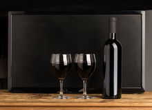 Bottle of wine and two glasses. Bottle with red wine and glasses on wooden table. Black background Stock Photo