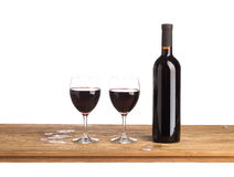 Bottle of wine and two glasses. Bottle with red wine and glasses on wooden table. Isolated background Stock Photography