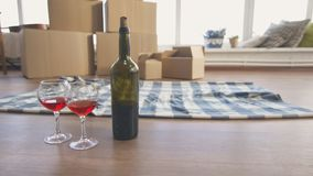 Moving to a new house, concept. A bottle of wine and two glasses with a rug on the background of boxes, a new home Royalty Free Stock Photos
