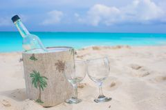 Bottle of wine and two glasses on sandy beach Stock Photo