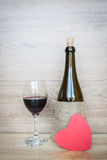 Bottle of wine and wine glass with heart on wood for background Royalty Free Stock Photography
