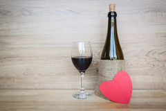 Bottle of wine and wine glass with heart on wood background stock photo