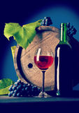 Bottle of wine and wineglass with grape near wooden vintage keg Stock Photos