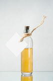 Bottle with yellow liquid and empty label on the light backgroun Stock Photo