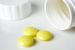 Bottle with yellow pills. White bottle with yellow pills stock image