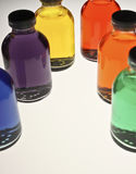 Bottled Colors. An abstract arrangement of six clear glass bottles with black caps, filled with different colored liquids: blue, purple, yellow, red, orange, and Stock Photos