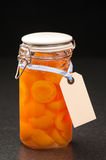Bottled Fruit. Bottled apricot halves in glass preserve jar with label stock photos