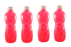 Bottled fruit juice. 4 Pink Bottled fruit juice isolated on a white background stock photography