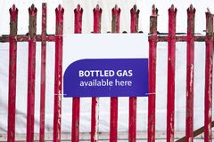 Bottled gas available here sign on red railing fence. Uk royalty free stock image