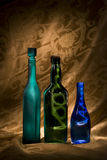 Bottled Lightening. Three colored bottles lit creatively to contain the light against a dramatic golden background Royalty Free Stock Images