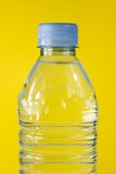 Bottled water. On yellow background Royalty Free Stock Photography
