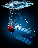 Bottled water. On a black/blue background with air bubbles stock images