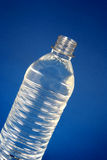 Bottled Water. Water bottle against a blue background Royalty Free Stock Image