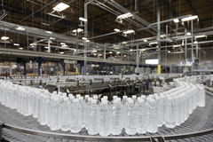 Bottled water on conveyor at bottling plant Stock Images