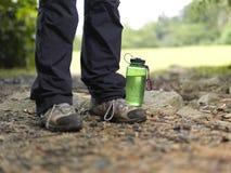 Bottled water at the foot of trekker's feet Stock Photo