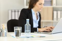 Bottled water in an office workplace. Bottled water in the foreground in an office workplace with an executive working in the background royalty free stock photo