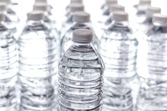 Bottled Water Rows. Bottled water with bright white light in the background. Generic, with no labels Royalty Free Stock Images
