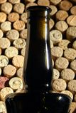 Bottleneck. Corked glass bottle of red wine. Side view. Background pattern of used bottles corks stock photos